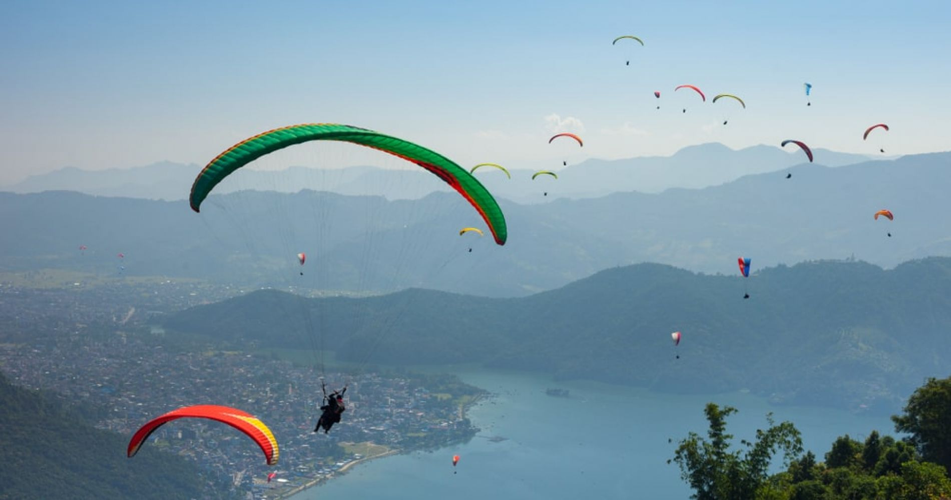 Watch Paragliders Launch and Glide above the skies of Pokhara in Nepal